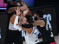 In this Aug. 30, 2020, file photo, Dallas Mavericks' Luka Doncic (77) is fouled by Los Angeles Clippers' Marcus Morris Sr. during the first half of an NBA basketball first-round playoff game in Lake Buena Vista, Fla. (AP Photo/Ashley Landis, File)