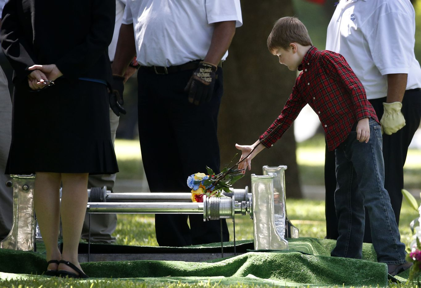 Magnus Ahrens, 8, son of fallen Dallas police officer Lorne Ahrens, drops flowers inside his father's grave in the Garden of Honor at Restland Funeral Home and Cemetery in Dallas on July 13, 2016. Ahrens and four other officers were gunned down during an ambush on police in downtown Dallas.