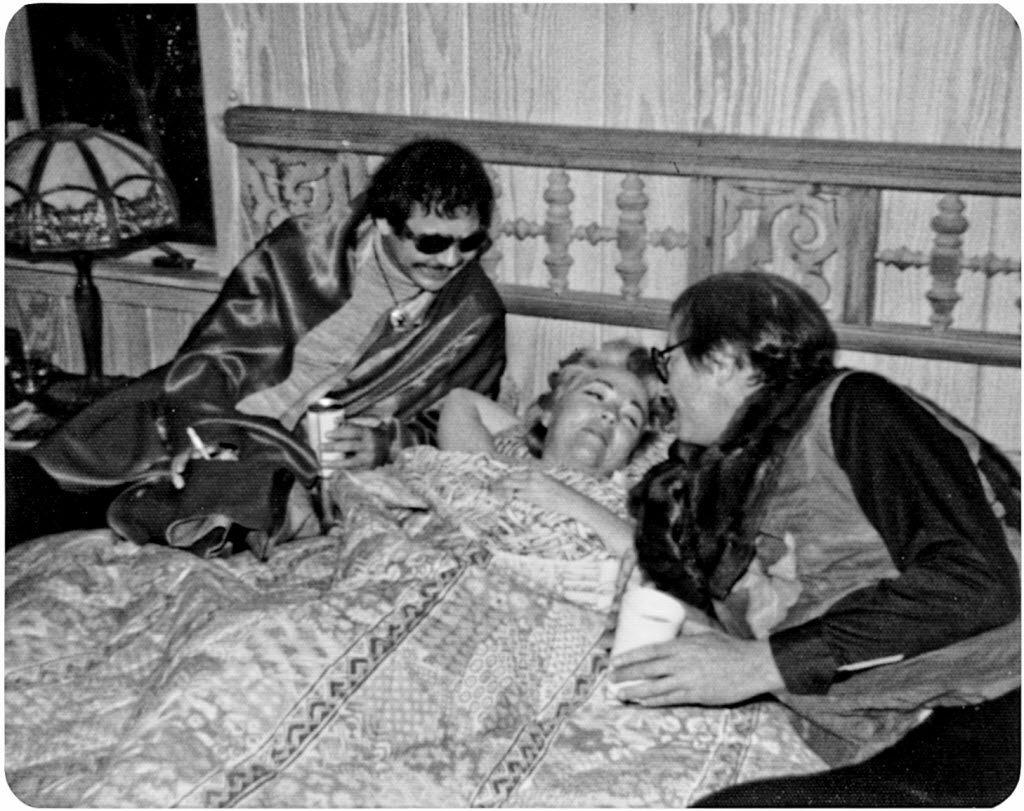 "Bud Shrake (right) and Gary Cartwright, dressed as ""Flying Punzars,"" wake Ann Richards early one Sunday morning.  (Courtesy Doatsy Shrake)"