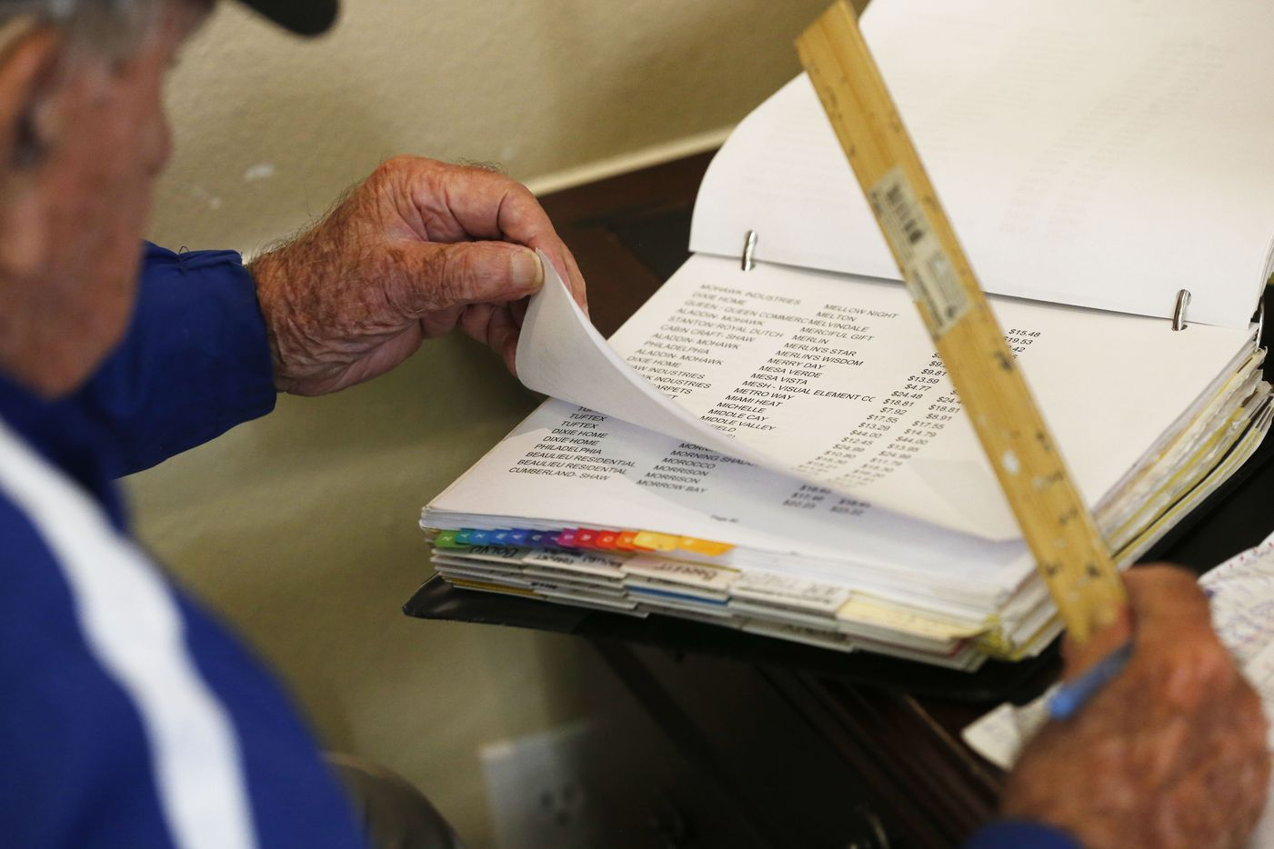 Chester Hollingsworth combs through a notebook looking for prices to put on a carpet pricing display chart at S&H Flooring in Dallas on Tuesday, October 24, 2017.