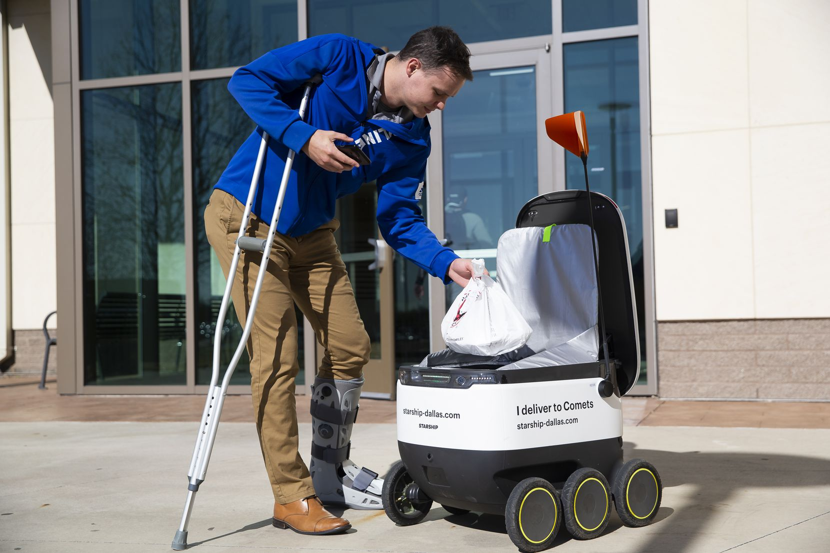 One of Starship Technologies' robots delivers Garrett Virgin food on UTD's campus in Richardson. Customers unlock the storage compartment of the robot by pressing a button in a smartphone app. (Juan Figueroa/The Dallas Morning News)