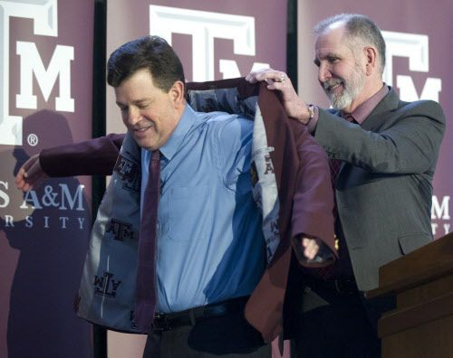 Texas A&M Univerity President Michael Young puts the maroon blazer on new Athletic Director Scott Woodward, officially welcoming him as a member of the A&M elite during a press conference at A&M in College Station, Texas, Monday, Jan. 11, 2016. (Dave McDermand/The College Station Eagle via AP)