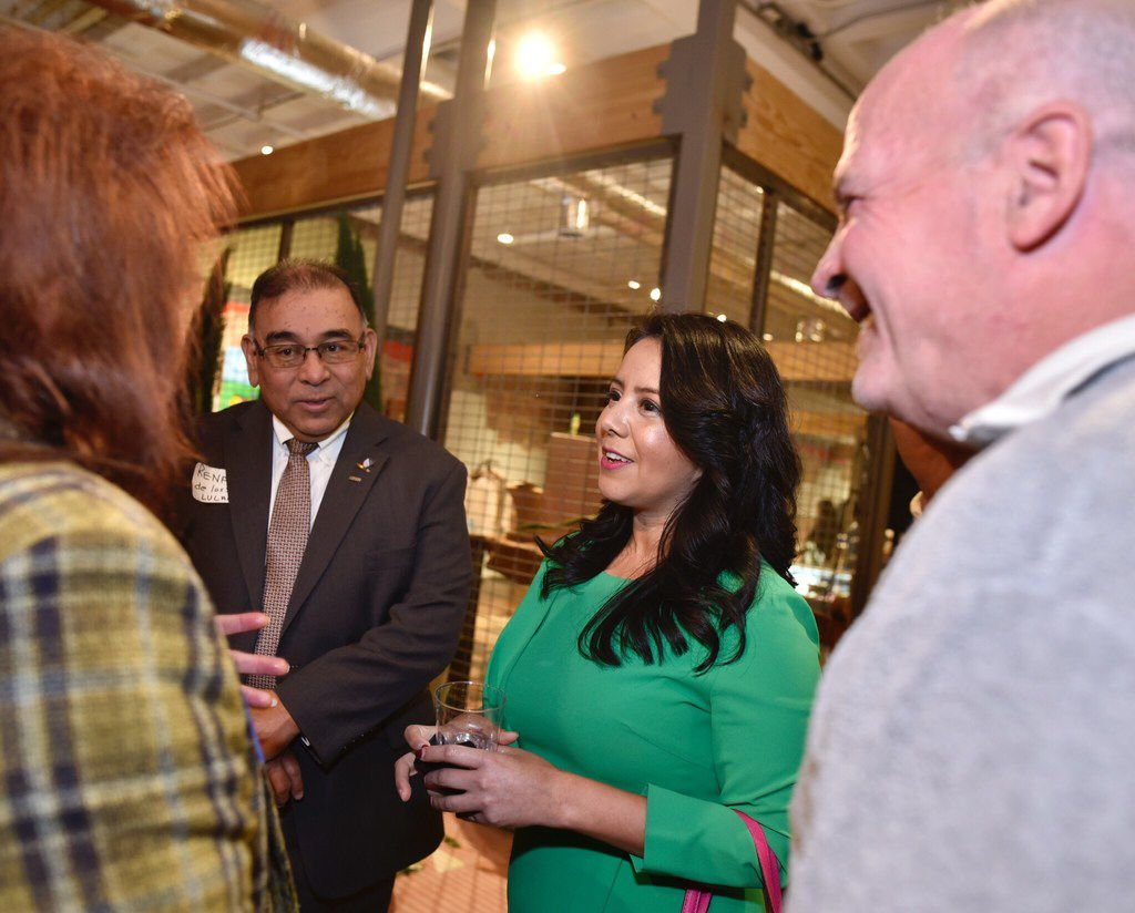 Rep. Victoria Neave mingles with other Hispanic leaders during an event hosted at Mercado369 on Friday, Jan. 4, 2019.