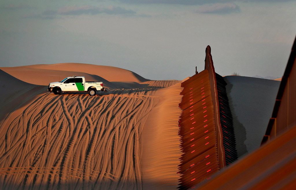 A U.S. Border Patrol agent surveys a section of fence that runs through the Imperial Sand Dunes along the international border with Mexico in Imperial County, Calif.