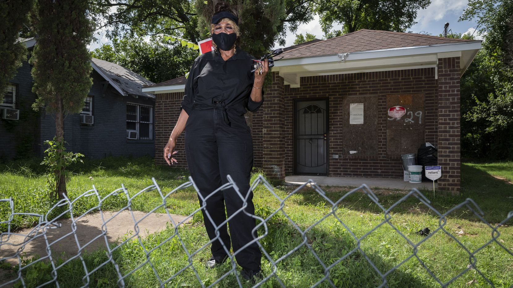 Doretha Traylor, 71, wearing a face mask, outside her soon to be home that is being repaired by the Shalom Builders of Texas, on July 14. Her home burned down after an electrical fire in 2013.