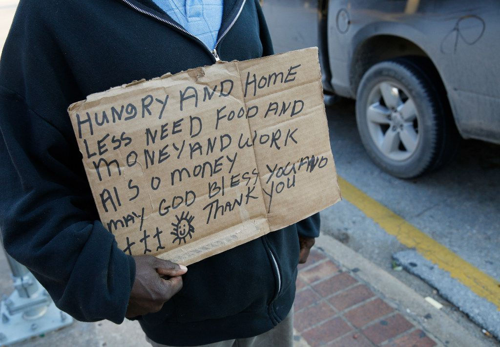 A homeless man solicits passing drivers for money at the intersection I-35E and Market Center in Dallas in 2019. Dallas City Council members say they want increased enforcement on panhandling in the city saying it's a health and safety issue.