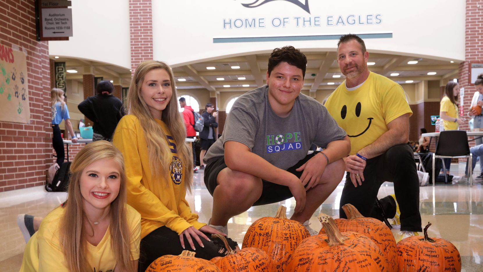 From left, Hope Squad members McKinley Bownds, Brooke McBride, Grehson Coates and teacher Tony Cooper at Prosper High School with a few of the pumpkins that students across the campus have signed as part of a thankfulness exercise.