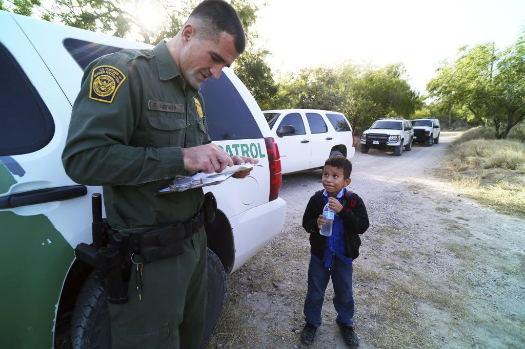 A Border Patrol agent reads the birth certificate of Alejandro, 8. The certificate was the only thing he brought with him as he and others crossed the Rio Grande near McAllen.