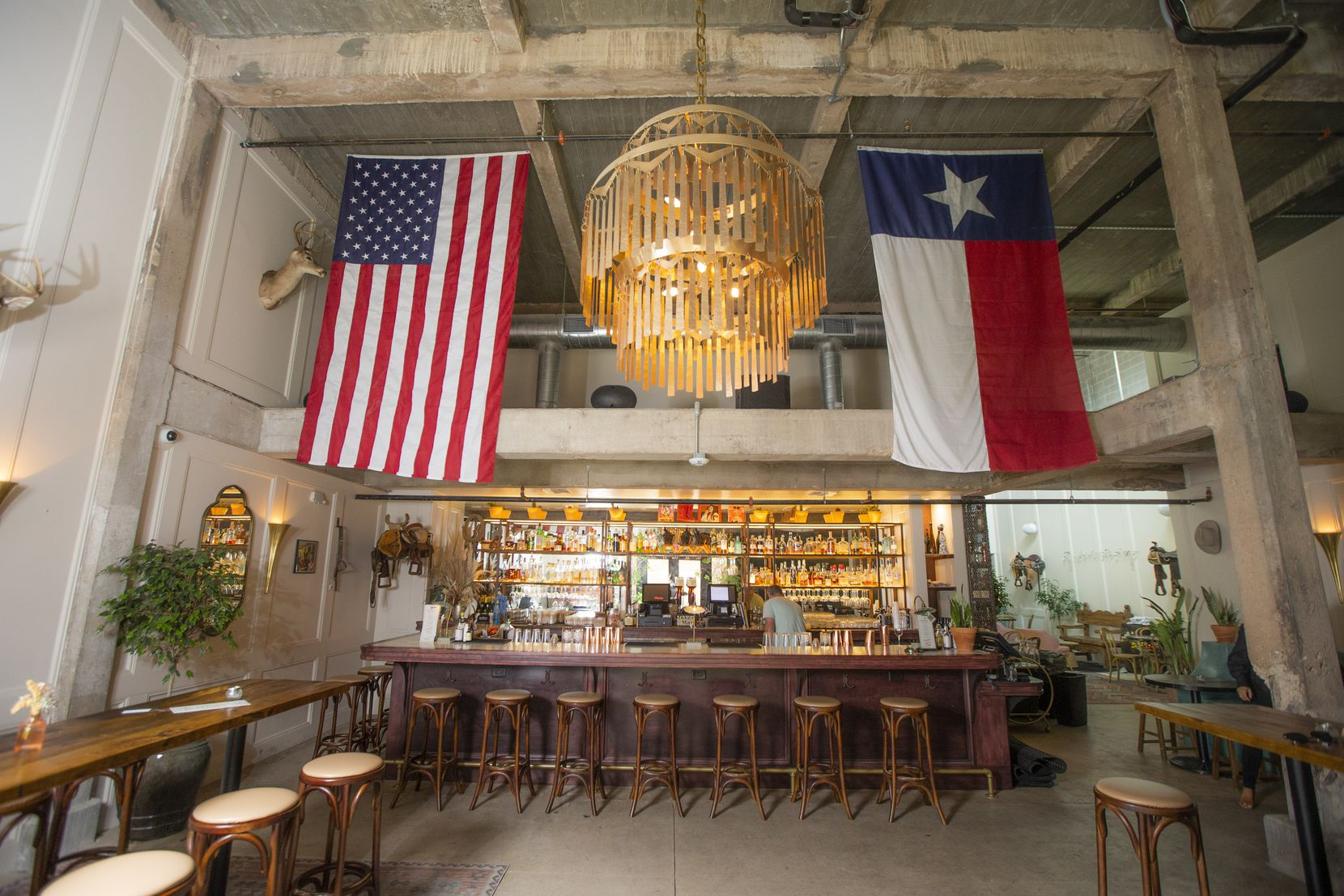 Upon entering, guests are greeted by American and Texan flags hanging over the bar at Side Saddle in the Fort Worth Stockyards
