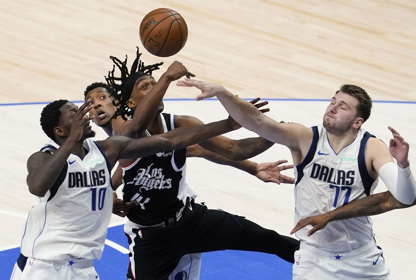 Dallas Mavericks guard Luka Doncic (77) an forward Dorian Finney-Smith (10) fight for rebound against LA Clippers guard Terance Mann (14) during the third quarter of an NBA playoff basketball game at American Airlines Center on Sunday, May 30, 2021, in Dallas.