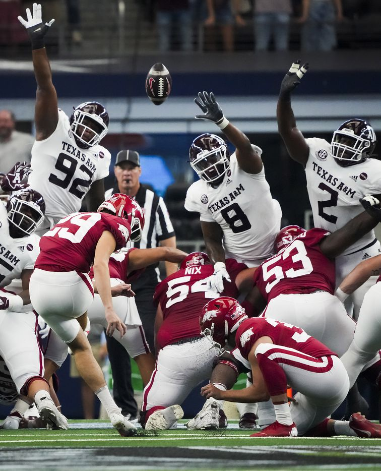 Arkansas place kicker Cam Little (29) kicks a field goal over Texas A&M defensive lineman Jayden Peevy (92), defensive lineman DeMarvin Leal (8) and defensive lineman Micheal Clemons (2) during the first half of an NCAA football game at AT&T Stadium on Saturday, Sept. 25, 2021, in Arlington.