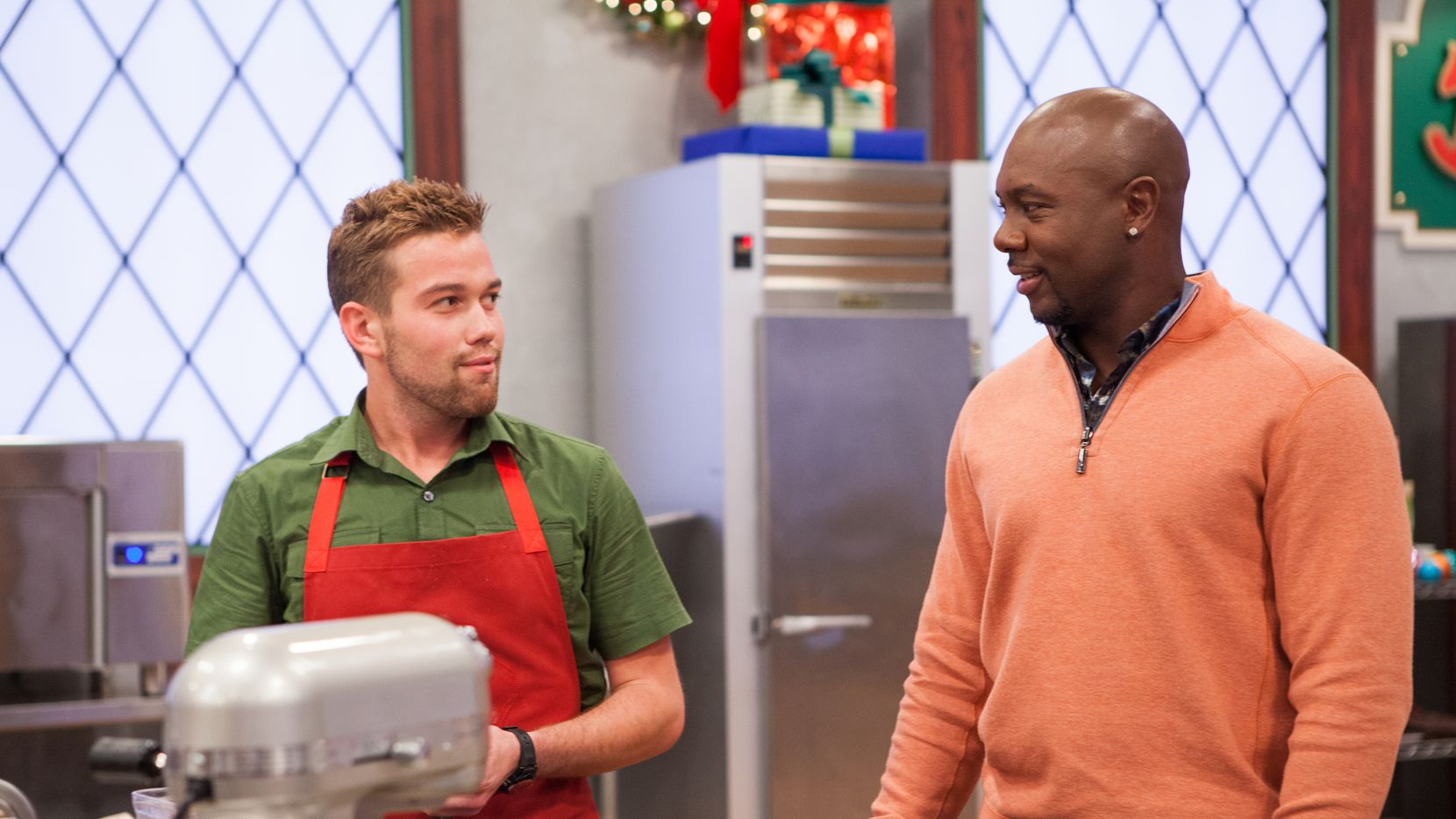 """Dylan Humphrey, left, and host Eddie Jackson talk about Dylan Humphrey's Family Tradition-themed Dark Chocolate Mocha Cup Cookie, Cranberry Spiced Platter Cookie with Lemon and Orange Zest, and Chocolate Raspberry Cookie with a Irish Cream Liqueur Filling and Royal Icing, on """"Christmas Cookie Challenge."""""""
