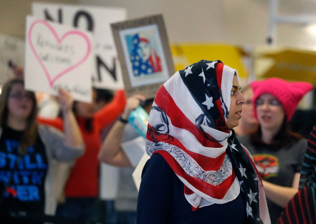 Protesters file through the waiting area at the international arrivals gate in Terminal D at DFW Airport on Sunday, January 29, 2017. (Louis DeLuca/The Dallas Morning News)