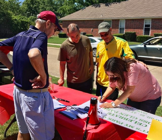 Bruce Hatter (left) signs up volunteers at one of the community events.