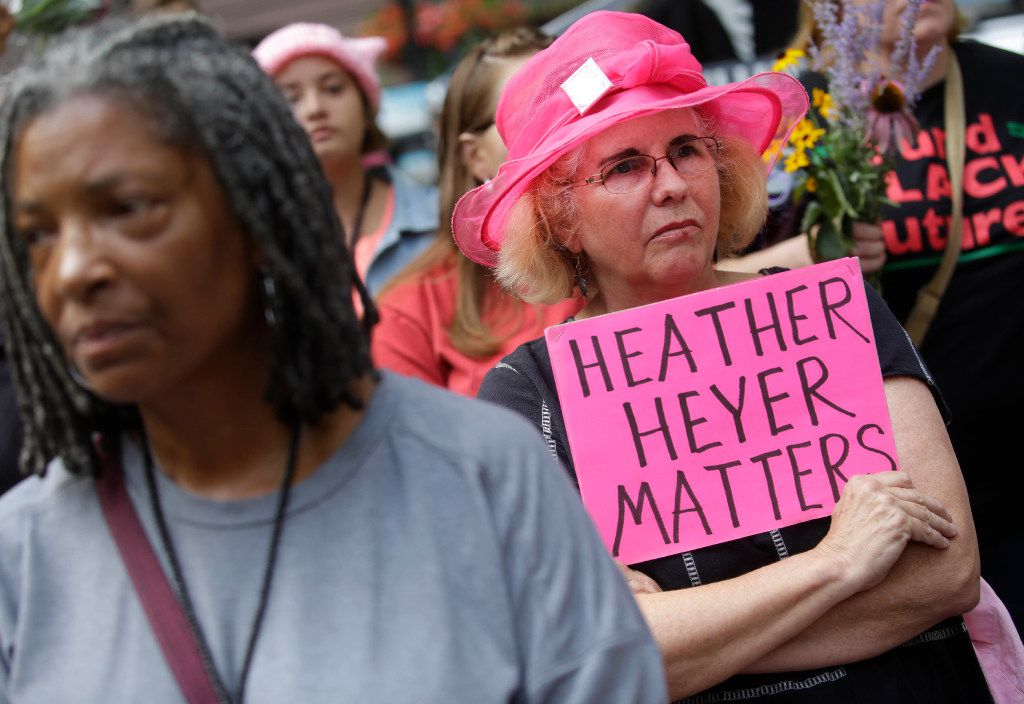 A womn holds a sign for Heather Heyer duering vigil August 13, 2017 in Chicago, Illinois for the victims in the previous day's violent clashes in Charlottesville, Virginia.  heather Heyer was killed and 19 people were injured in the city of Charlottesville when a car plowed into a crowd of people after a rally by Ku Klux Klan members and other white nationalists turned violent. Two state police officers died in a helicopter crash near the area.    / AFP PHOTO / Joshua LottJOSHUA LOTT/AFP/Getty Images