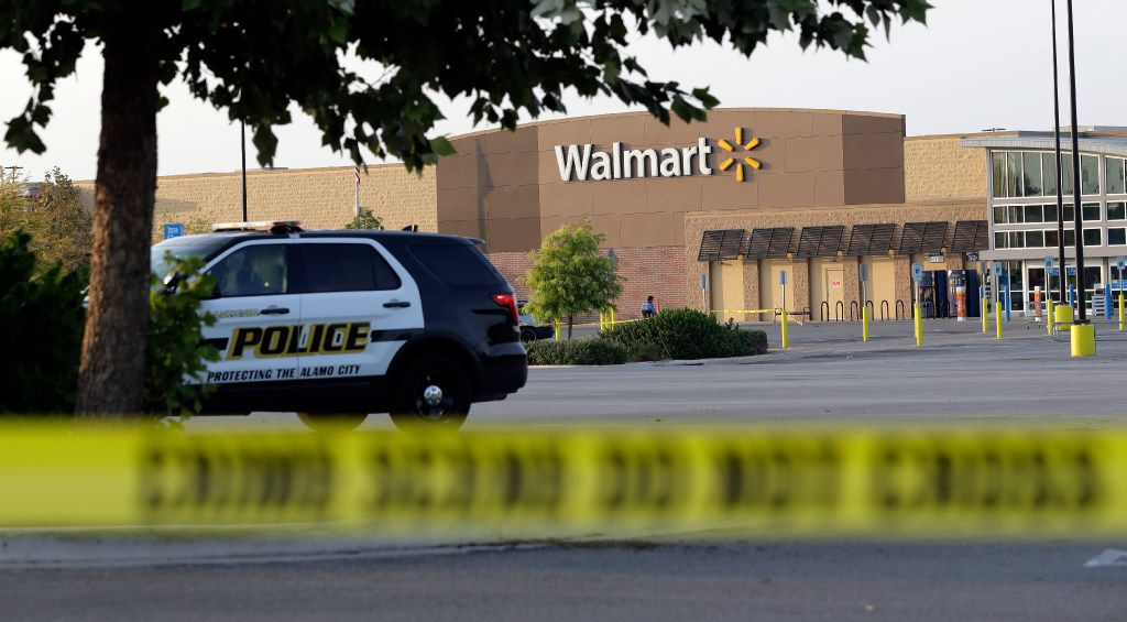San Antonio police officers investigate the scene where eight people were found dead in a tractor-trailer loaded with at least 30 others outside a Walmart store in stifling summer heat in what police are calling a horrific human smuggling case, Sunday, July 23, 2017, in San Antonio.