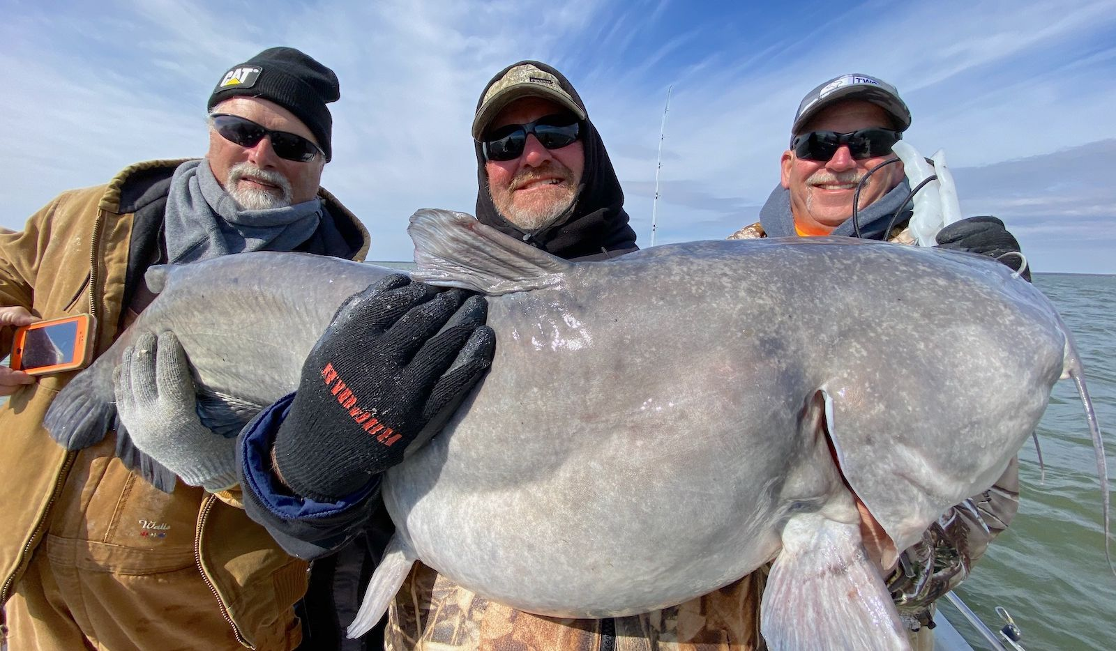 Kenny Quiett of Delia, Kansas (center) with the 80-pound blue catfish he landed on Feb. 15 at Lake Tawakoni. Veteran fishing guide Noel Ibarra put the angler on the fish while drifting in about 34 feet water. The fat cat ate a six-inch piece of gizzard shad rigged on a 8/0 circle hook. Ibarra rigs with a 30-pound test monofilament main line and 100-pound test mono leader.