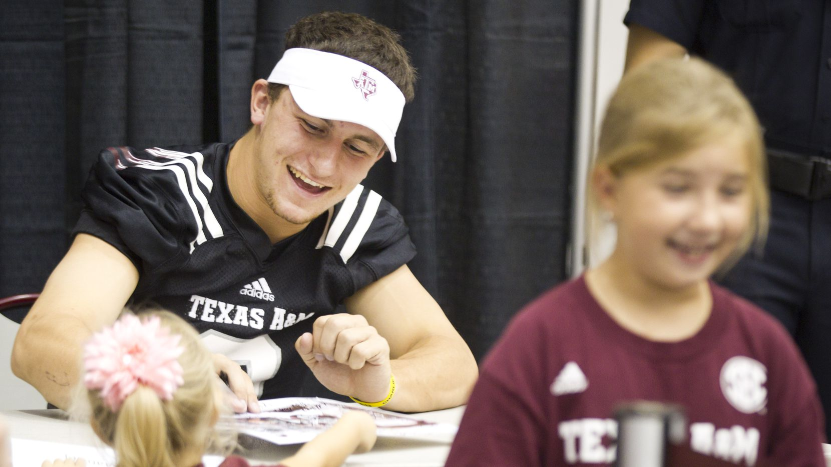 """Texas A&M quarterback Johnny Manziel signs autographs during the """"Meet the Aggies"""" event Saturday, Aug. 24, 2013, in College Station. Fans of the Texas A&M football team flocked to the Gilliam Indoor Track Complex to collect autographs and meet the Aggie players, one week prior to the team's season opener against Rice. ( Brett Coomer / Houston Chronicle ) ORG XMIT: 498538 08252013xSPORTS"""
