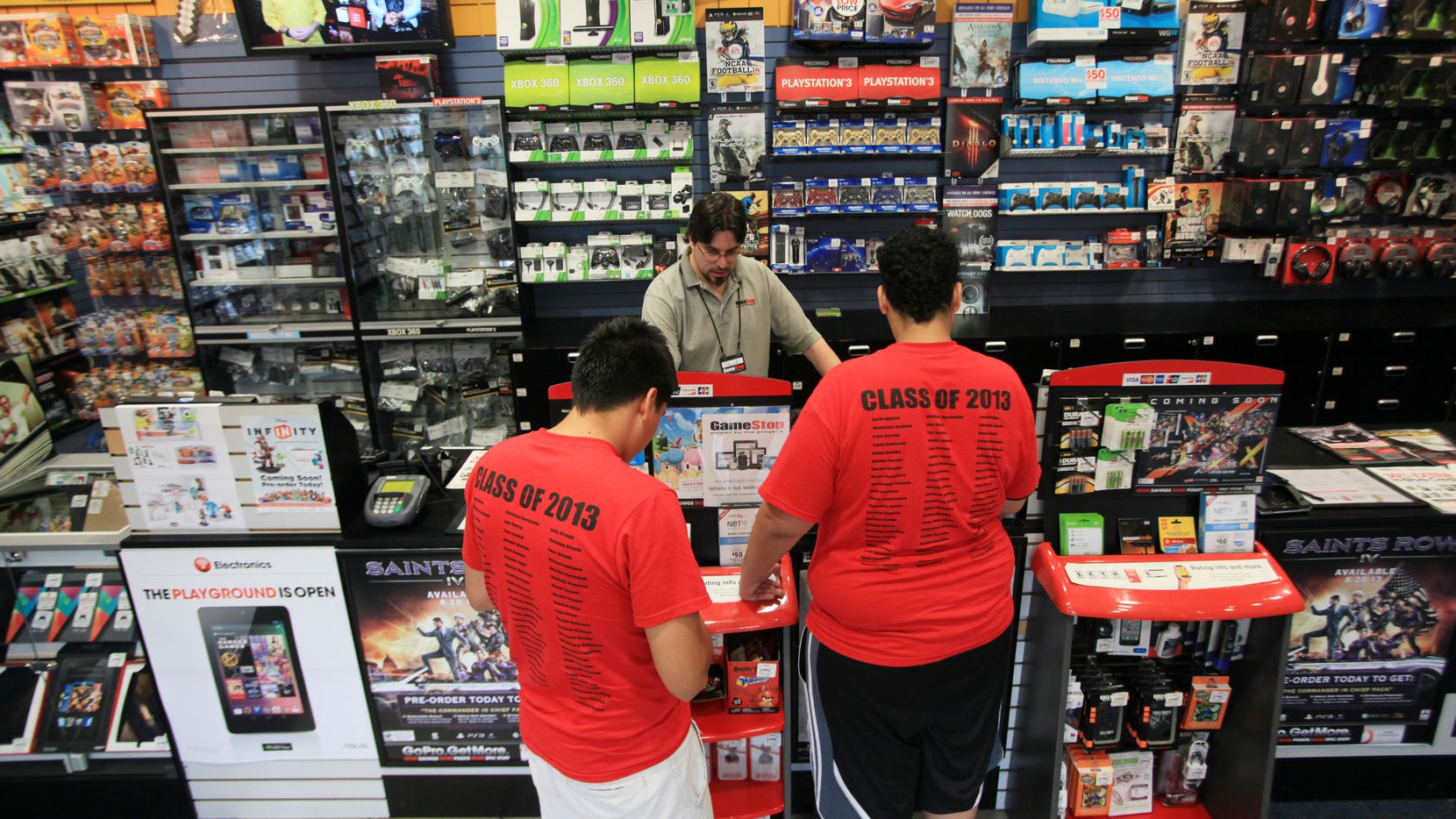 GameStop manager David Green, center, helps two customers at the store inside NorthPark Center, on May 23, 2013 in Dallas.