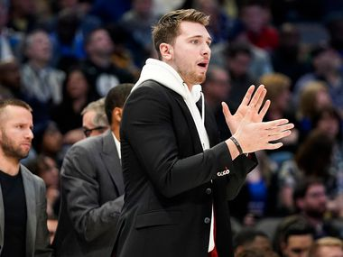 Injured Dallas Mavericks guard Luka Doncic encourages his teammates from the bench during the second half of an NBA basketball game at American Airlines Center on Wednesday, Feb. 5, 2020, in Dallas.