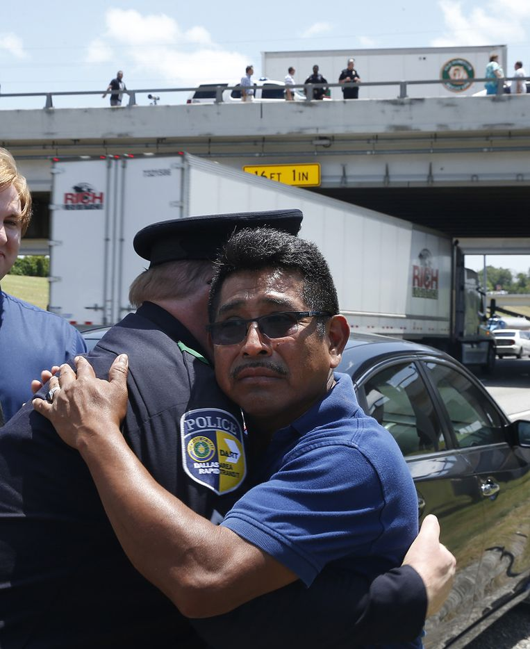 DART Corporal Gary Hutchison is hugged by Marino Castro, Dallas, after a funeral procession for DART Officer Brent Thompson on Interstate 20 in Duncanville, Texas on Wednesday, July 13, 2016. Thompson and four other officers were killed during an attack during a peaceful Black Lives Matter protest on July 7, 2016.