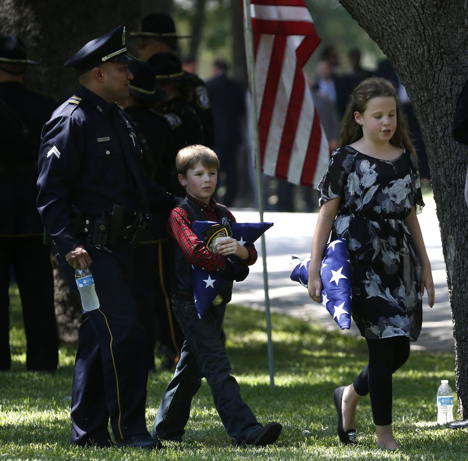 Dallas police officer Jaime Castro walks with Sorcha Ahrens, 10, (right) and Magnus Ahrens, 8, the children of fallen Dallas police officer Lorne Ahrens, during their his burial in the Garden of Honor at Restland Funeral Home and Cemetery in Dallas on July 13, 2016. Ahrens and four other officers were gunned down during an ambush on police in downtown Dallas.