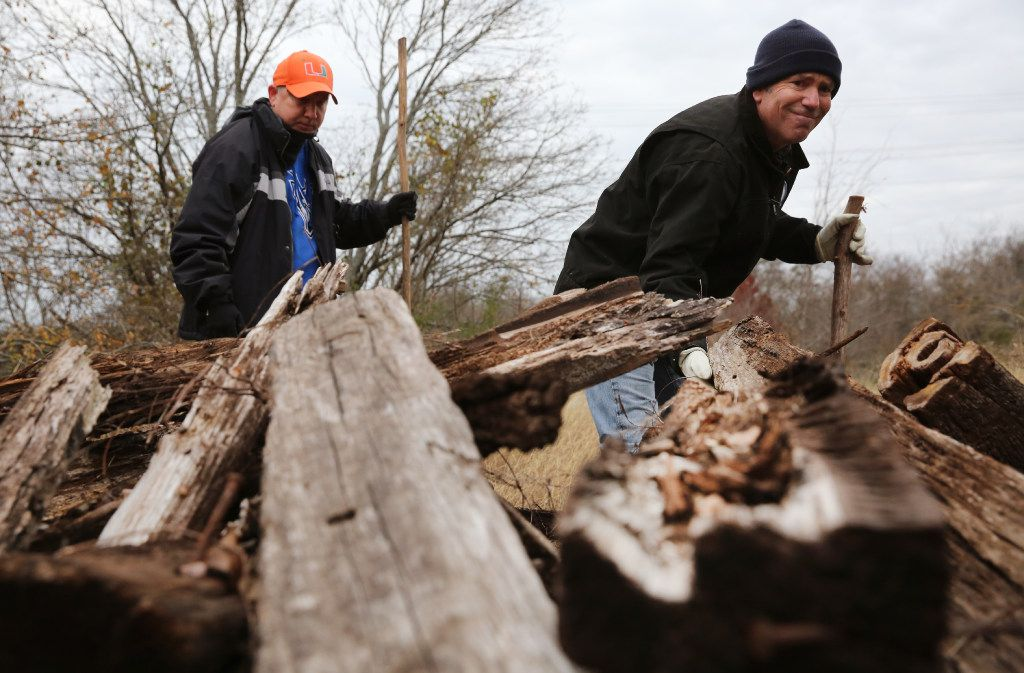 Mark Morris (right) and Clint Jenkins look beneath a pile of wood in northern Collin County during a weekly search for clues to the whereabouts of Mark's daughter, Christina.