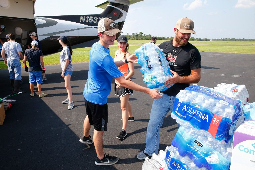 Dalan Jones (from left) Kyndal Jones and Ashton Hunter unload water and supplies from a private plane from Georgetown a week after Hurricane Harvey at the Orange County Airport in Orange, Texas, on Sept. 2, 2017.