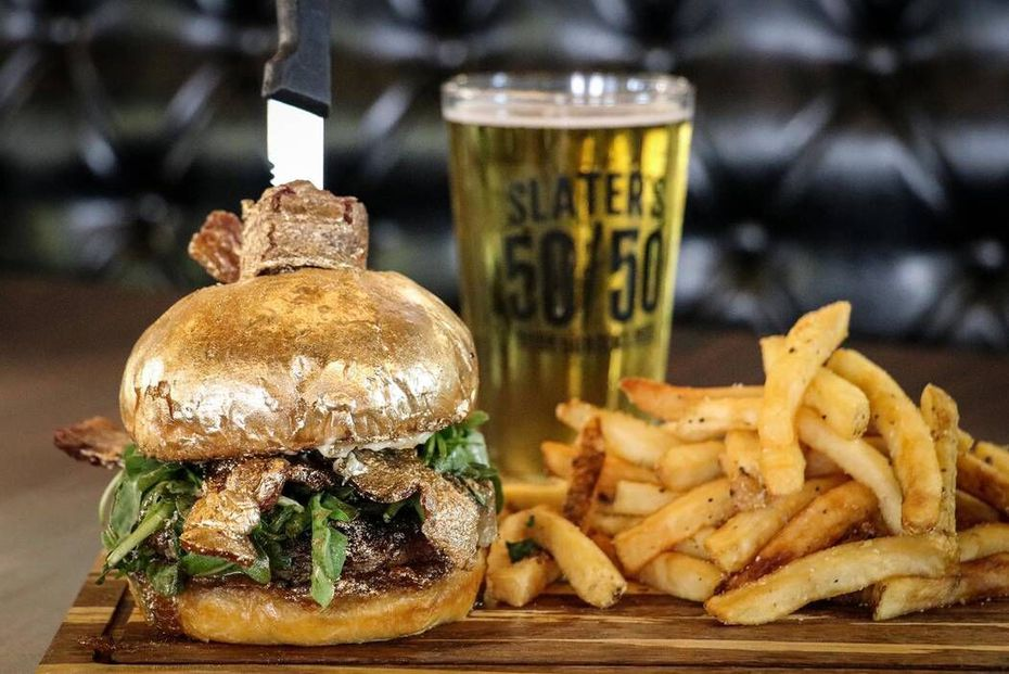 "At remaining Slater's 50/50 restaurants, this ""NYE Ball Drop 24 Karat Burger"" will be served. It comes with the bacon and the bun dusted in 24-karat gold."