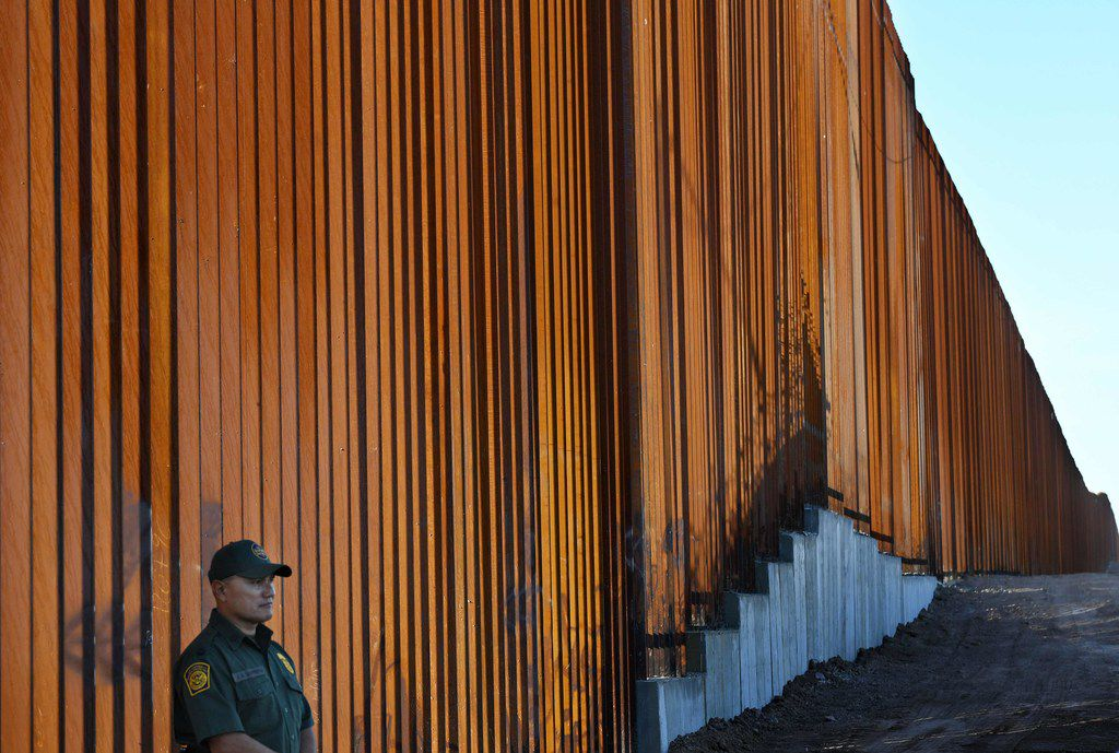 A Border Patrol officer keeps watch at the border wall in the El Centro Sector at the U.S.-Mexico border in Calexico, California.