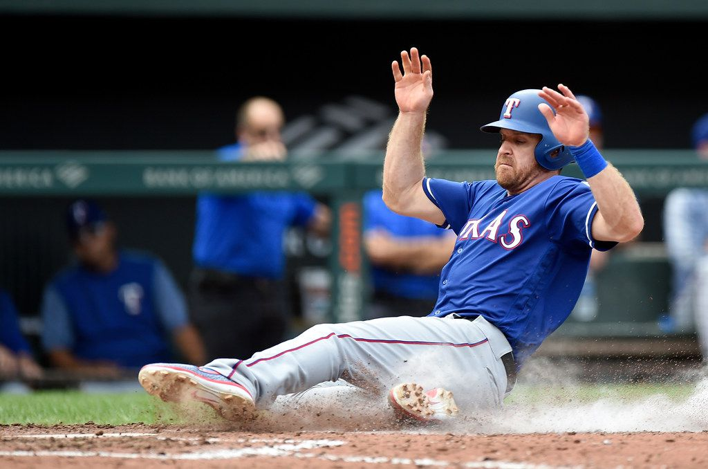 BALTIMORE, MD - SEPTEMBER 08:  Logan Forsythe #41 of the Texas Rangers slides into home plate and scores in the sixth inning against the Baltimore Orioles at Oriole Park at Camden Yards on September 8, 2019 in Baltimore, Maryland.  (Photo by Greg Fiume/Getty Images)