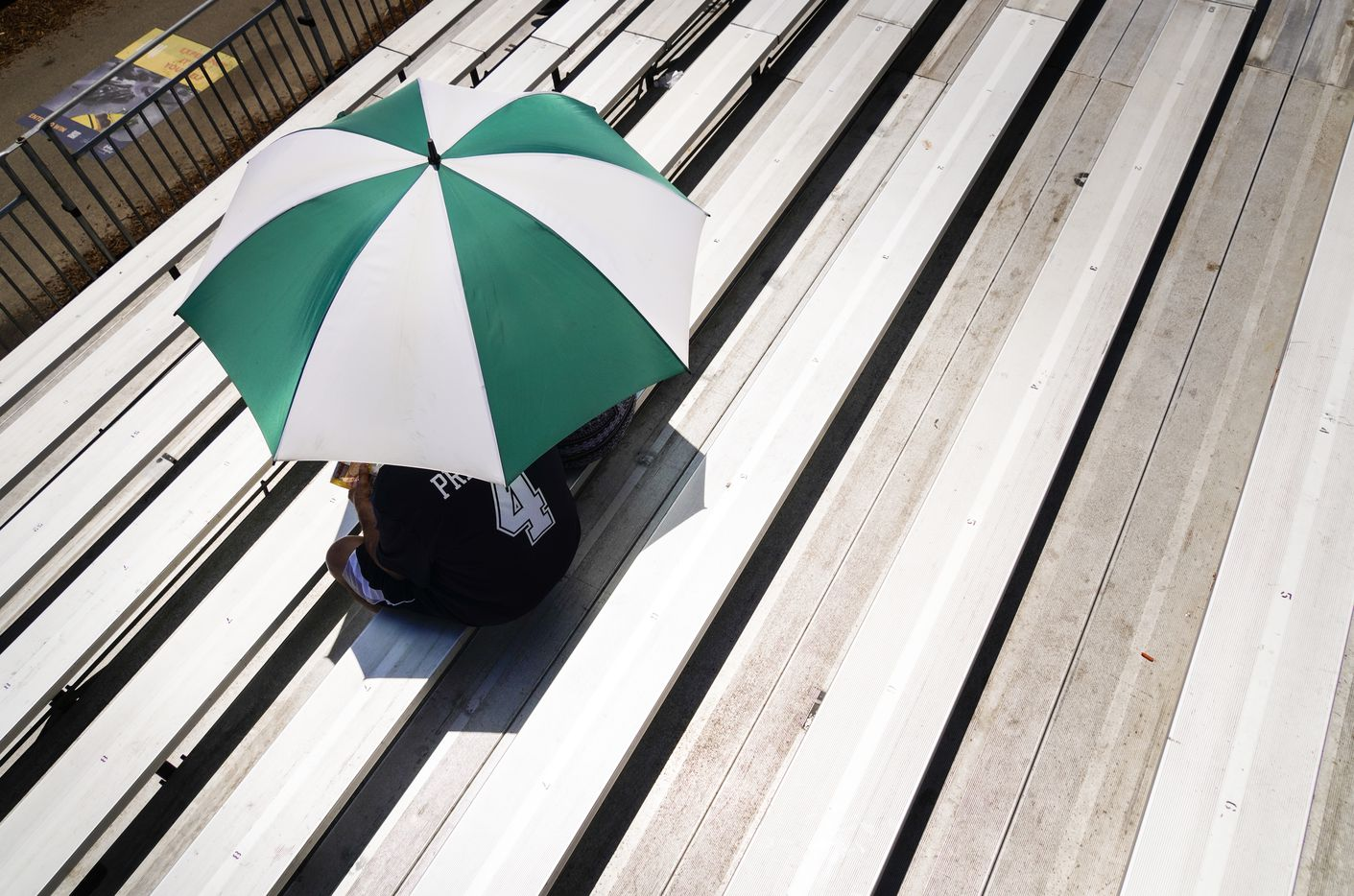 Dallas Cowboys fans find shade under an umbrella as they watch the team practice at training camp on Wednesday, July 28, 2021, in Oxnard, Calif.