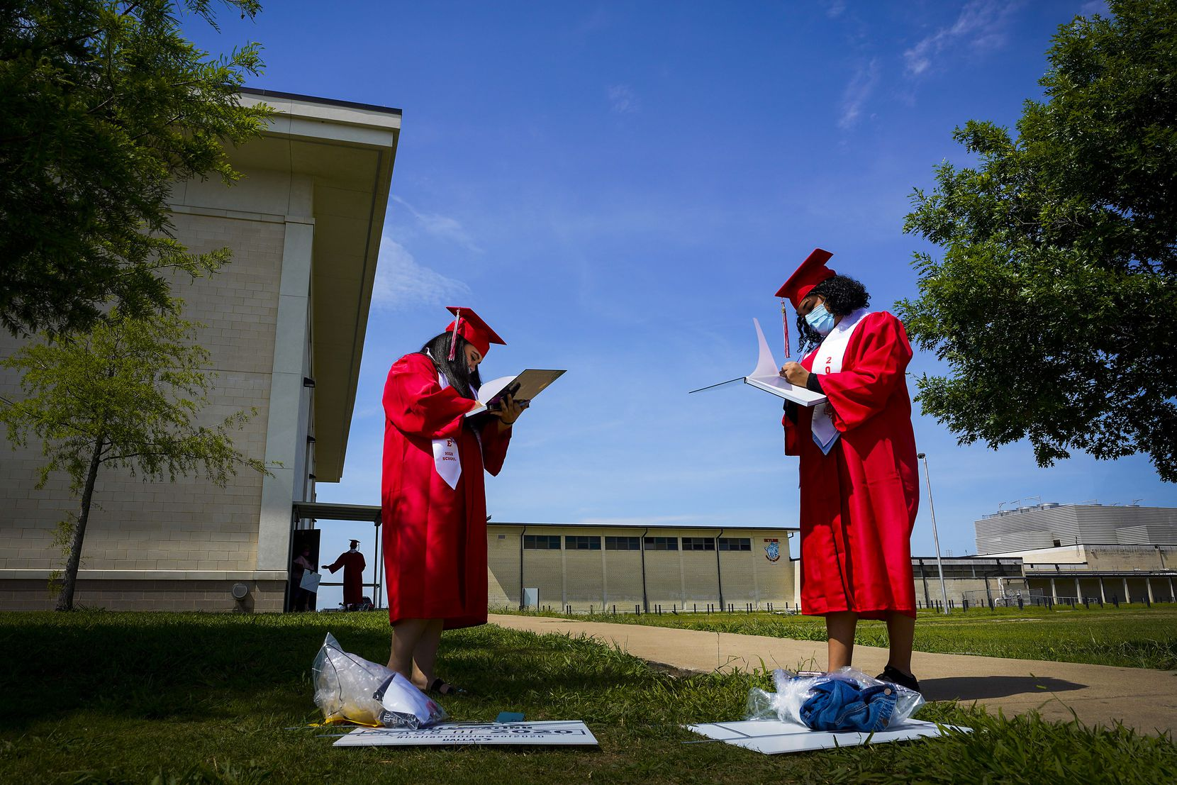 Seniors Andrea Soto (left) and Samanta Zuniga signed each other's yearbooks after picking up their graduation caps and gowns at Skyline High School in Dallas on May 11, 2020.