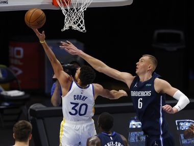 Golden State Warriors guard Stephen Curry (30) attempts a shot in front of Dallas Mavericks forward Kristaps Porzingis (6) during the second quarter of play at American Airlines Center on Saturday, February 6, 2021 in Dallas.