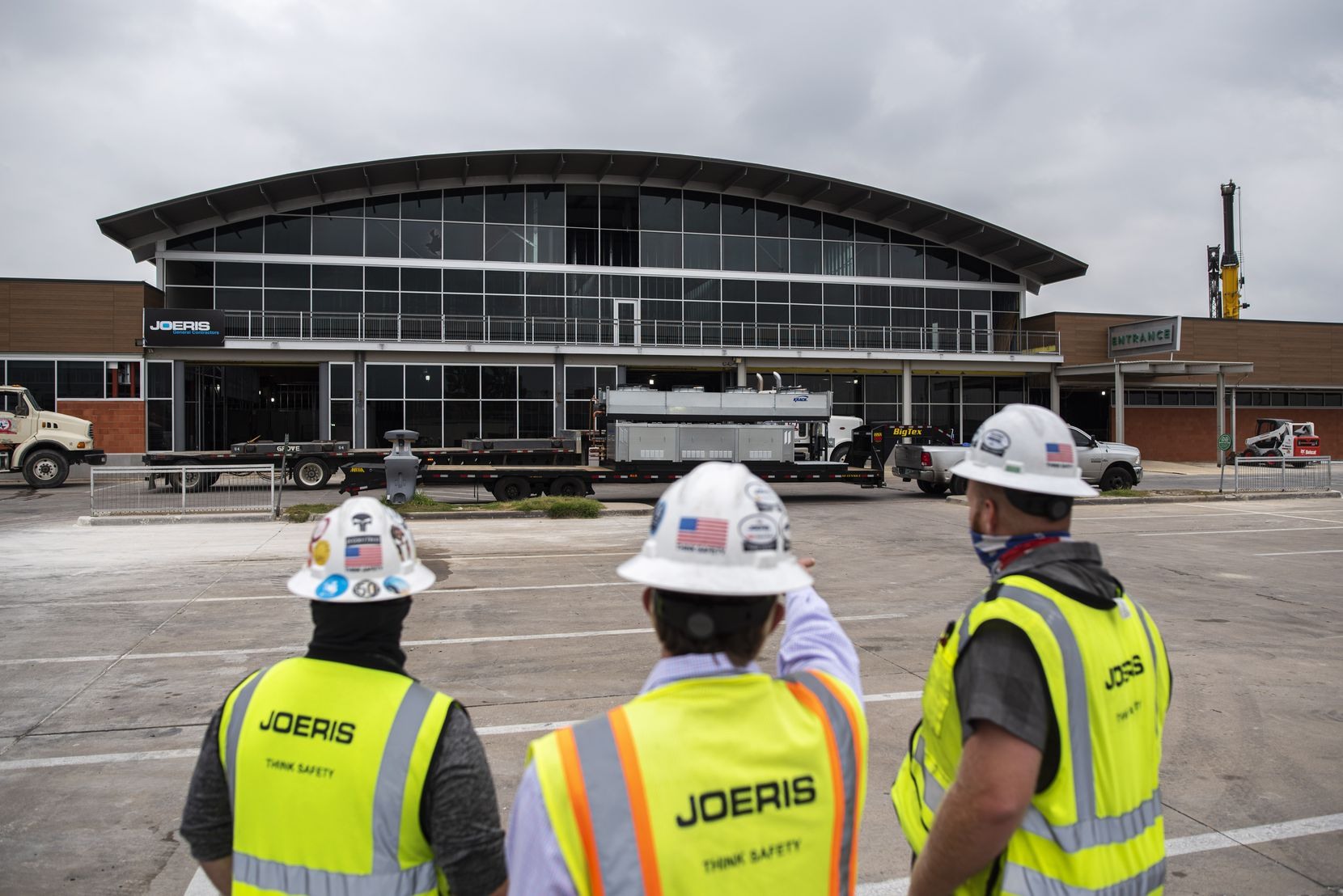 From left: Superintendent Ben Lawrence, project manager Zach Wernette and superintendent Dean Womble talk outside the construction site for the Central Market at the Preston Oaks shopping center in Dallas. The grocery store will reopen next year.