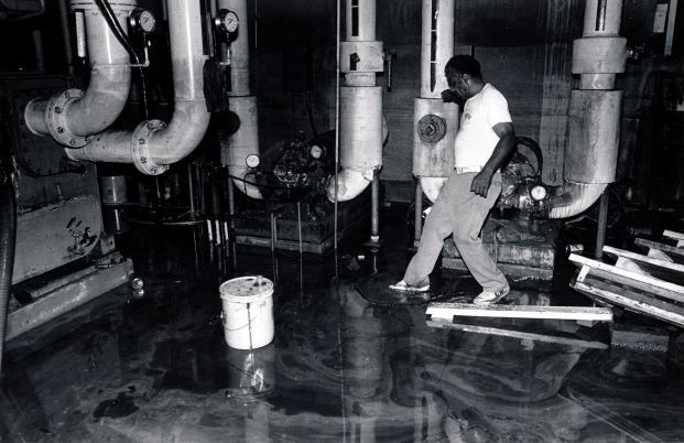 A Dallas Power & Light employee steps through the flooded underground area where cables ignited.
