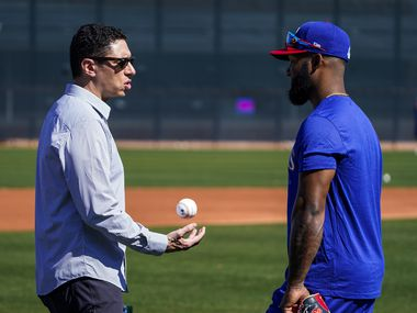 Texas Rangers general manager Jon Daniels tosses a baseball while chatting with outfielder Danny Santana during a spring training workout at the team's training facility on Saturday, Feb. 15, 2020, in Surprise, Ariz.