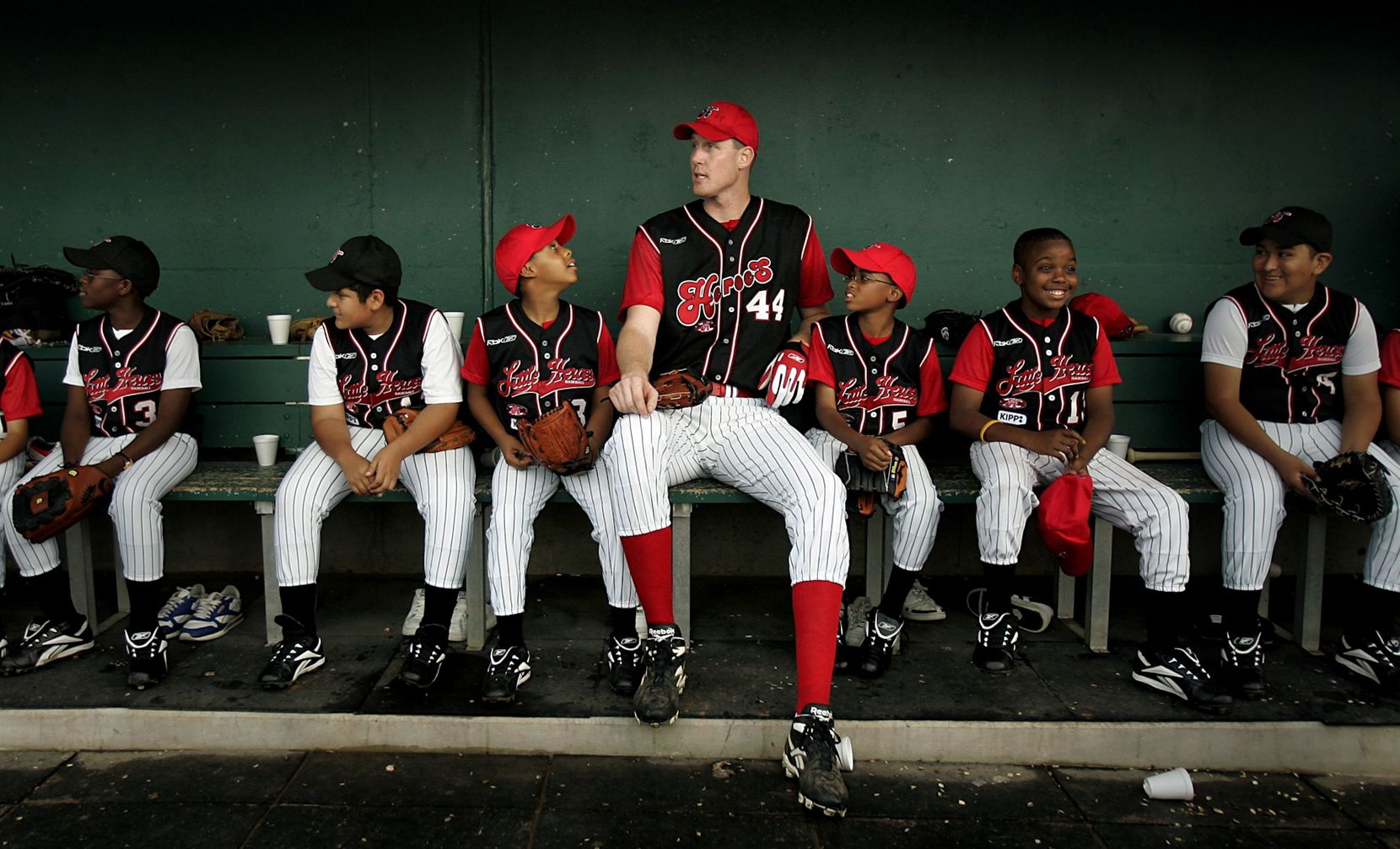Dallas Mavericks center Shawn Bradley relaxes in the dugout with a group of young baseball players from the KIPP TRUTH Academy before the 2005 Reebok Heroes Celebrity Baseball Game at Dr. Pepper/Seven Up Ballpark in Frisco, Saturday, July 16, 2005. The charity game, featuring local sports stars and national celebrities benefited the children's charities of the Mike Modano Foundation, the Todd Wagner Foundation and the Little Heroes Baseball Field Foundation.