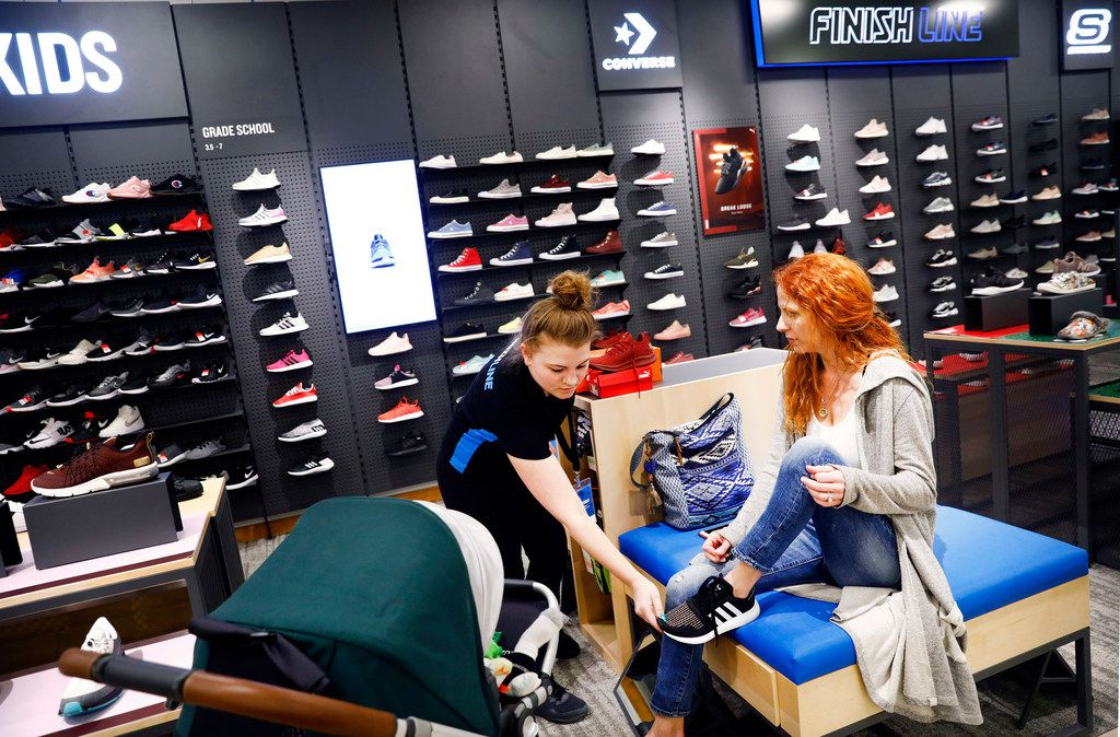 A Finish Line shoe store is new to the Macy's store at NorthPark Center. Here, store manager Rachel Luna (left) helps Lauren Gardner of Dallas with a pair of sports shoes. The shoe store is part of upgrades to Macy's.