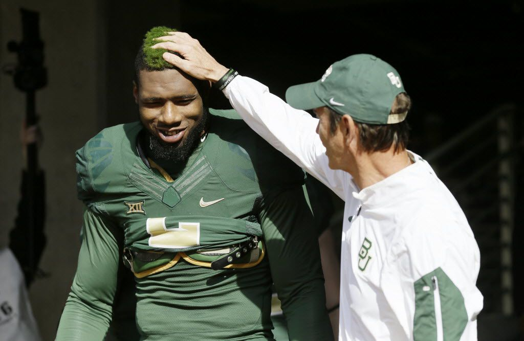 Baylor defensive end Shawn Oakman (2) gets a pat from head coach Art Briles before an NCAA college football game Saturday, Dec. 5, 2015, in Waco, Texas. Oakman was arrested Wednesday, April 13, 2016, on a charge of sexually assaulting a woman at his Texas apartment, Waco police said. (AP Photo/LM Otero)