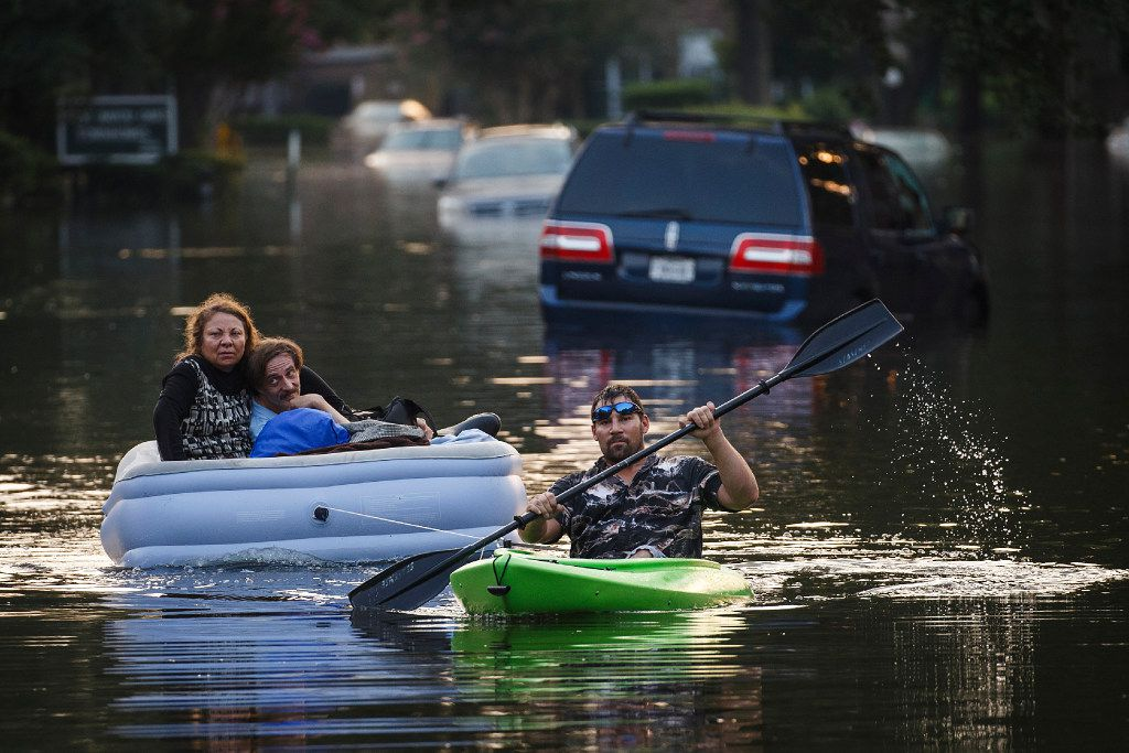Franklin Moor tows a couple behind his canoe as he helps residents of a west Houston apartment complex check on their homes and retrieve belonging on Sunday, Sept. 3, 2017, in Houston.  The area remains flooded from Hurricane Harvey.