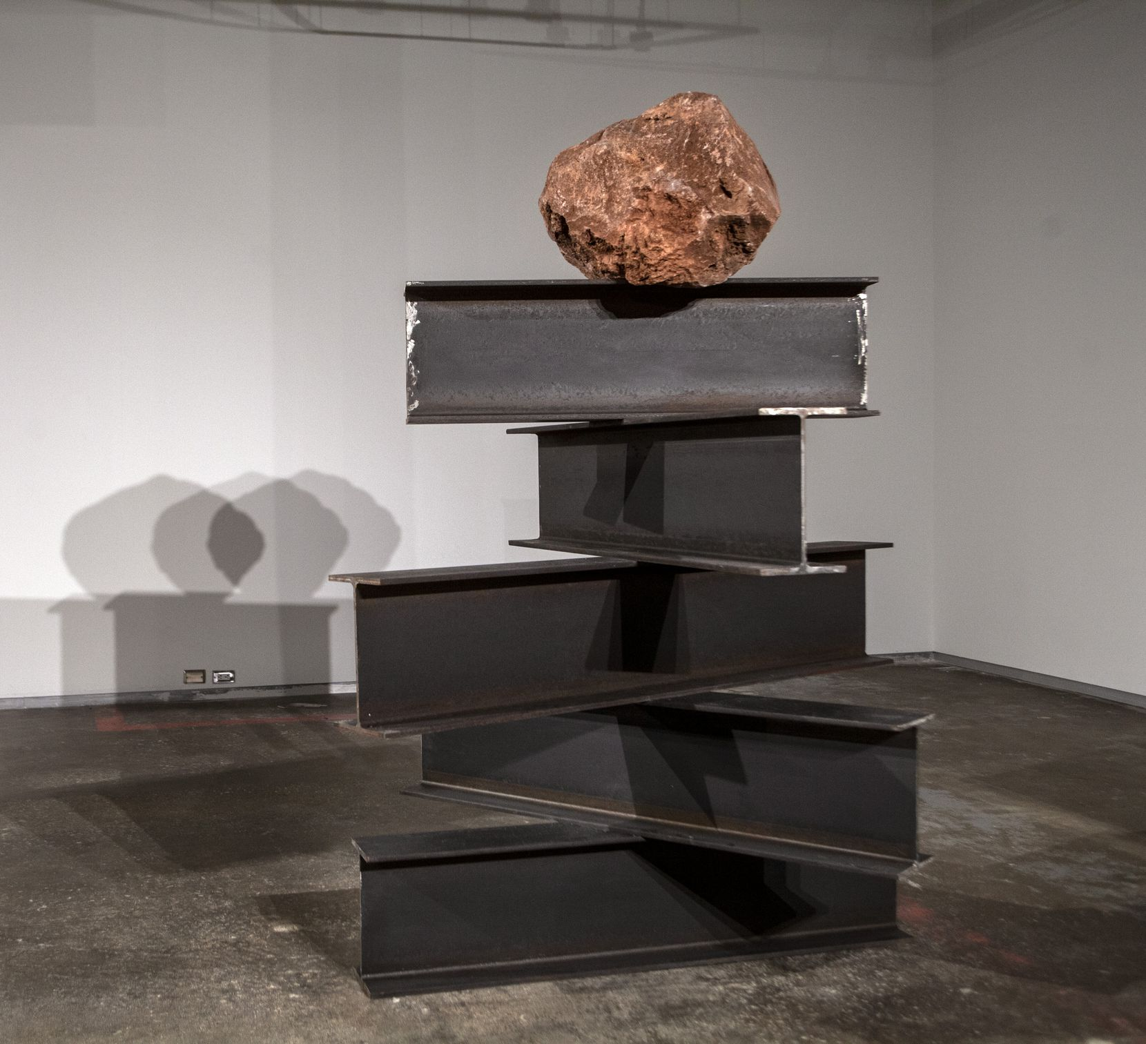 "The 2019 work ""Perpetuum Mobile"" features a volcanic rock perched atop metal beams."
