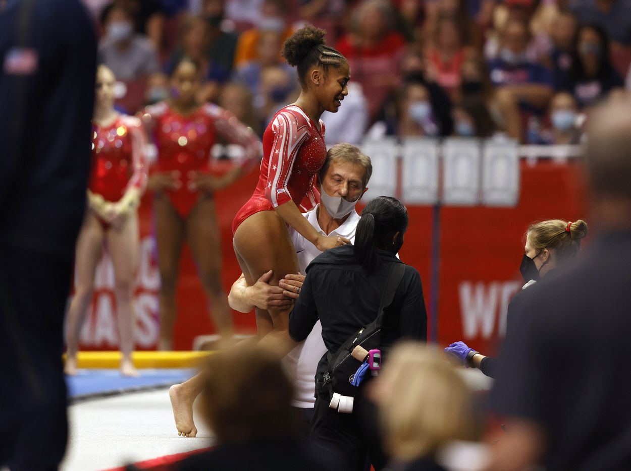 Skye Blakely of WOGA is helped off the vault station by coach Evgeny Marchenko after injuring herself during warmups prior to competing in day 1 of the women's 2021 U.S. Olympic Trials at America's Center on Friday, June 25, 2021 in St Louis, Missouri.(Vernon Bryant/The Dallas Morning News)