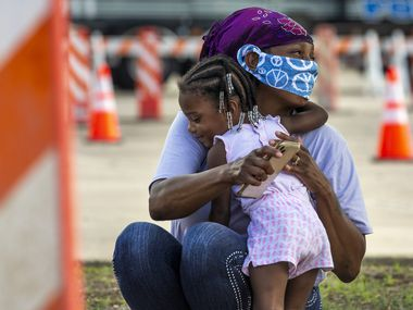 """Tammy Washington gets a hug from her 2-year-old granddaughter, Aria, 2, as they and their family waits for a hotel voucher after driving all night from Orange, Texas, to reach the Mesquite Reception Center set up for hurricane evacuees on Wednesday. Weather forecasters have said Hurricane Laura is expected to make landfall in Southeast Texas and Western Louisiana at midnight on Thursday. """"There will be a lot of devastation,"""" said Texas Governor Greg Abbott in a press conference."""