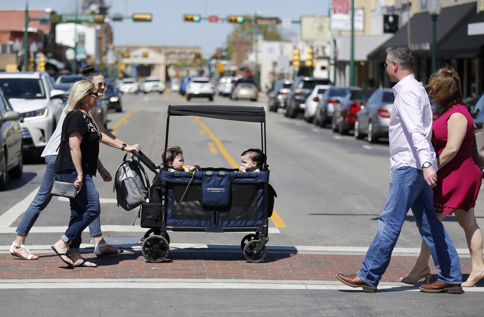 People watch as Celia Moorman of Frisco walks with Jenny Marr as she pushes her quadruplets Hudson, Henry, Hardy, and Harrison Marr on Friday, March 26, 2021, in Grapevine, Texas.