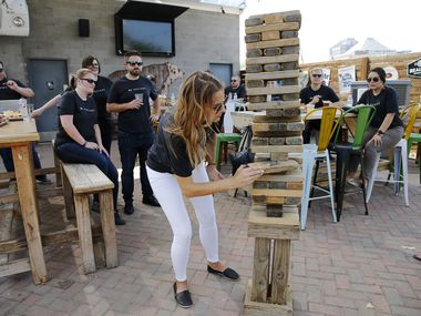Emily Schroeder carefully removed a block of wood as she competed in a game of Jenga during an employee appreciation event for Valiant Residential employees.