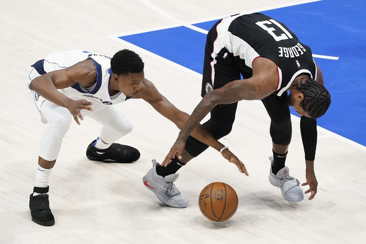 Dallas Mavericks guard Josh Richardson (0) fights for a loose ball with LA Clippers guard Paul George (13) during the third quarter of an NBA playoff basketball game at American Airlines Center on Sunday, May 30, 2021, in Dallas.