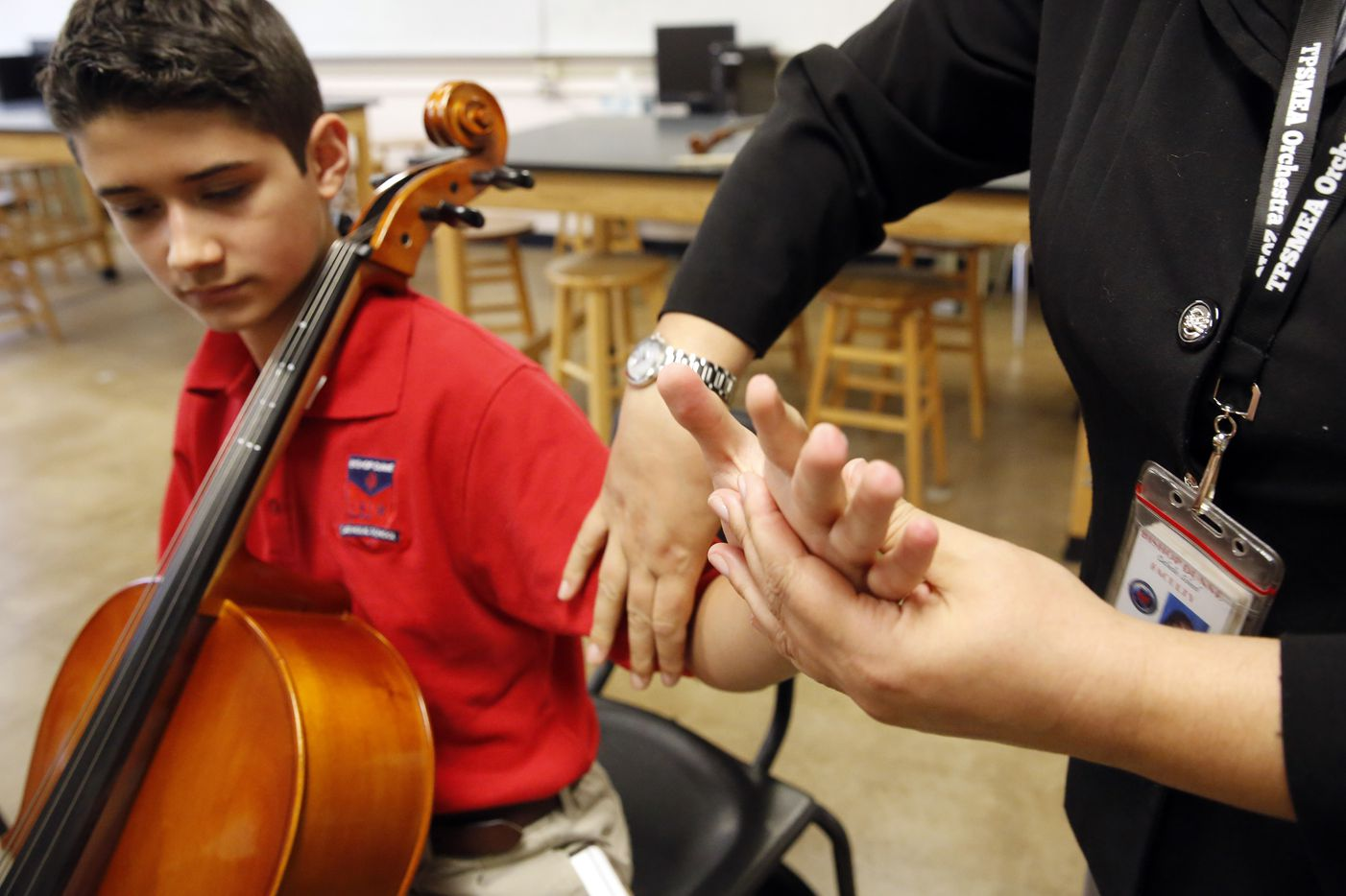 Instructor Julia Gray-Lion guides Zach on the arm motion he will use to play the cello, during his second lesson at Bishop Dunne Catholic School in Dallas.