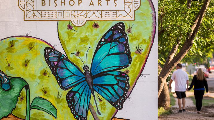 """Pedestrians walk past a temporary installation of paintings of flora and fauna at Bishop and Melba streets in the Bishop Arts District, A resident told The Guardian that Bishop Arts """"was sleepy. There were a handful of spots, but it was not remotely the entertainment destination it is today."""""""