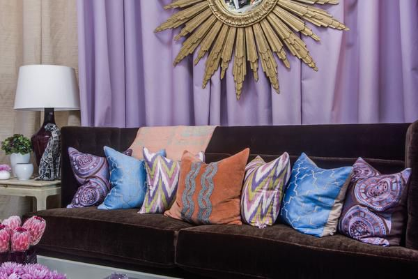 Mecox The Knox-Henderson retailer's vignette features a chocolate sofa layered with pillows in a pastel colorway. Piles of pillows are a way to inject personality in a setting. Note the gold starburst mirror.